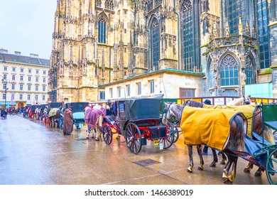 VIENNA, AUSTRIA - MARCH 2, 2019: The line of carriages with blanketing horses during winter days next to Stephansdom, on March 2 in Vienna