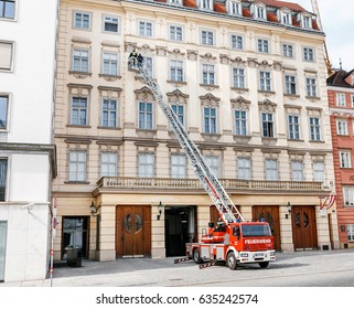 VIENNA, AUSTRIA - MARCH 23, 2017: Firefighters with a car on an extended staircase near a multi-storey building