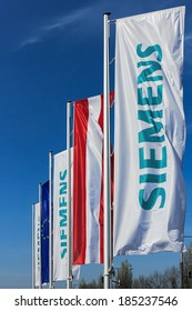 VIENNA, AUSTRIA - March 30, 2014:  Flags bearing the Siemens logo in front of their Austrian company headquarters. Siemens City is a campus-like complex with space for 6000 employees.