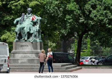 Vienna, Austria - May 11th 2012: A statue of Goethe with remote and popcorn props and two people admiring it.