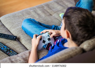 VIENNA, AUSTRIA - MAY 4th, 2018: kid boy playing Xbox. Xbox is a video gaming brand created and owned by Microsoft of the United States