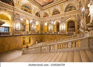 Vienna, Austria - Nov, 2017: Illuminated sumptuous staircase in imposing interior of Naturhistorisches Museum (Natural History Museum) with statues and round arches.