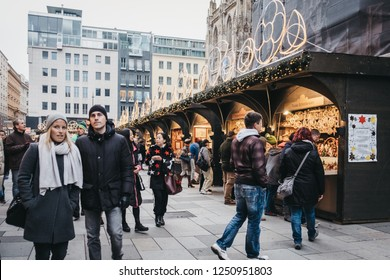Vienna, Austria - November 24, 2018: People walking past Christmas market stall near St. Stephen Cathedral, the most important religious building in Vienna.