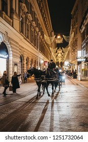 Vienna, Austria - November 24, 2018: Horse carriage tour on a street in Vienna, Austria, in the evening. These tours are very popular amongst tourists.