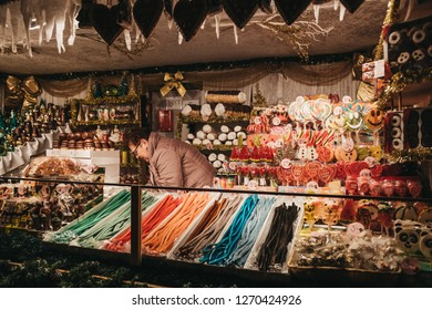 Vienna, Austria - November 24, 2018: Seller at a food stand at Christmas World on Rathausplatz, traditional Christmas Market in Vienna with over 150 booths offering food, drinks, sweets  and crafts.