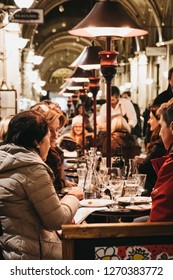 Vienna, Austria - November 25, 2018: People enjoying food and drinks at outdoor tables of a restaurant in Vienna, a popular tourist destination in Europe.