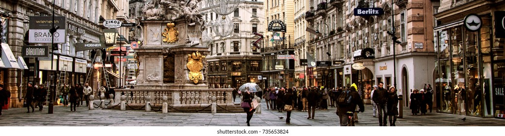 VIENNA, AUSTRIA - NOVEMBER 26, 2013: City center Graben street with shops and restaurants full of people in Vienna, Austria. Pestsaule sculpture showing the Holy Trinity on a corinthian column