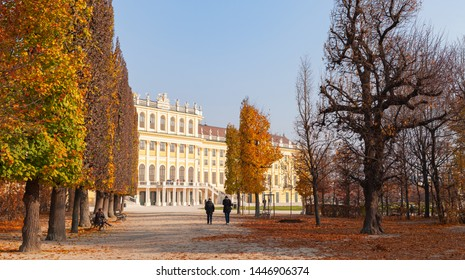 Vienna, Austria - November 3, 2015: People walk at Schonbrunner Schlosspark gardens. Schonbrunn Palace main facade in the background