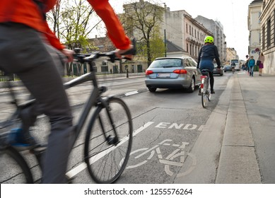 Vienna, Austria - Oct, 2018: Dangerous encounter between cyclists and cars at the end of a marked bike path on busy road. Conflict situation on a multi-used street.