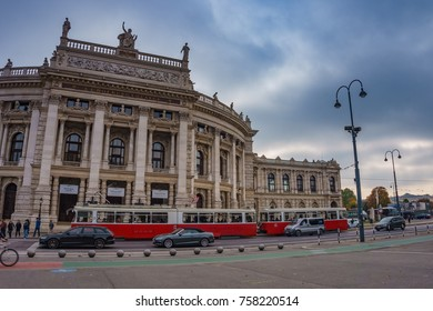 Vienna, Austria - October 2017: View of Vienna State Opera House Staatsoper in the afternoon. Front facade of Burgtheater with a red tram and people on the square. Vienna, Austria, Europe.