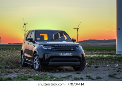 VIENNA, AUSTRIA - OCTOBER 21, 2017: Land Rover Discovery 5 in the journey across Europe. Photo taken in the Austria with wind turbines and sunset in the background.