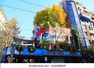 Vienna, Austria - October 27, 2019: Hundertwasserhaus apartment block has colorful facade, undulating floors, roof covered with earth and grass, large trees growing from inside the rooms