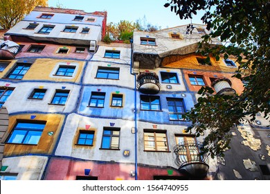 Vienna, Austria - October 27, 2019: The Hundertwasserhaus apartment block has colorful facade, undulating floors, a roof covered with earth and grass, and large trees growing from inside the rooms