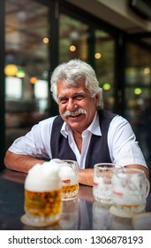 VIENNA, AUSTRIA - OCTOBER 29, 2016: Portrait of a happy senior waiter at the famous Beer Garden Schweizerhaus of Vienna making a little break with some pitchers of Budweiser beer in front