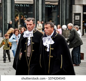 Vienna, Austria - October 30, 2007: two men in traditional vintage black costumes with white collars walking in the street