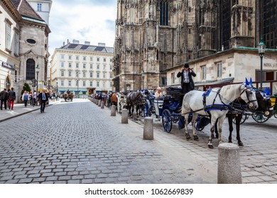 VIENNA, AUSTRIA - SEPTEMBER 12, 2013: Perspective view of a cobblestone street with horses, coaches and people walking by in the city center of Vienna September 12, 2013.
