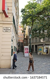 Vienna, Austria - September, 2019: Asian tourists visiting the old town with historic buildings and shady trees at Schottentor between the streets Schottengasse and Mölker Steig.