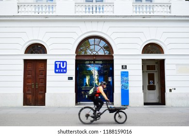 "VIENNA, AUSTRIA - SEPTEMBER 25, 2018: Bike riding man and entrance of the main building of Technische Universität Wien, shortly TU Wien (Eng. ""Vienna University of Technology"") at Karlsplatz, Vienna"