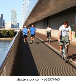 VIENNA, AUSTRIA - SEPTEMBER 6, 2011: Pedestrians walk and cyclists ride on September 6, 2011 in Danube river bridge, Vienna. Vienna is often quoted among most bicycle and pedestrian friendly cities.