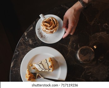 Vienna Coffee (popular traditional Austrian cream-based coffee beverage) topped with whipped cream and cocoa powder, and Esterhazy torte on a marble table. Vienna desserts
