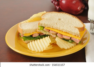 A vienna sausage and cheese sandwich with milk and fruit