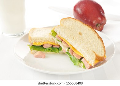 Vienna sausage sandwich with an apple and milk on a high key setting