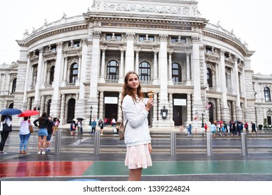 Vienna State Theater Burgtheater, Austria. A girl in a pink dress stands on the background of the building.