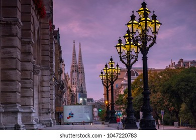 VIENNA/AUSTRIA - 22 SEPTEMBER 2017: Beautiful ornate lamp posts outside Rathaus Vienna, glow in the twilight. The Votivkirche is in the background