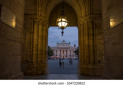 VIENNA/AUSTRIA - 22 SEPTEMBER 2017: Long shot of Burgtheater in Vienna framed through the arch of Rathaus as the theatre lights come on