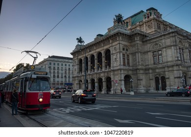 VIENNA/AUSTRIA - 22 SEPTEMBER 2017: Old tram pulls away from stop with the Vienna Opera House Behind. Taken early evening in September as the city lights are coming on