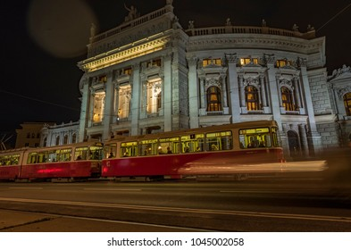 VIENNA/AUSTRIA - 22 SEPTEMBER 2017: Static low angle night shot of tram arriving at stop in front of Burgtheater in Vienna
