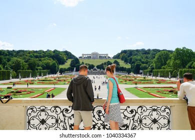 VIENNA,AUSTRIA - SEPTEMBER 4;  Young couple tourists  view  gardens  leading to Neptune Fountain and Gloriette in landscaped grounds of Schonbrunn Imperial Palace September 4 2017 Vienna Austria