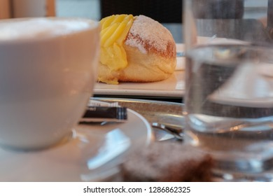 Viennese breakfast with coffee called melange and a vanilla donut or doughnut called Vanillekrapfen