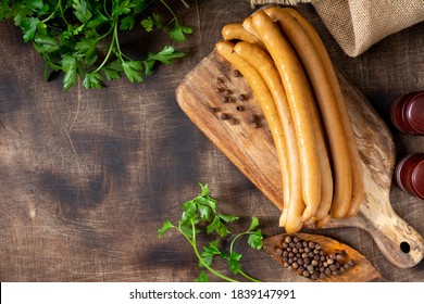 Viennese sausages on a wooden serving Board on a brown wooden table. Top view with a copyspace