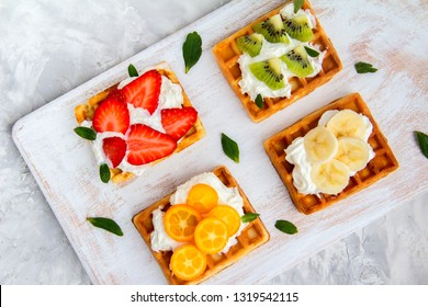 Viennese waffles with berries. Waffles with strawberries, kiwi, kumquat, Banana. Freshly baked waffles onwhite background.Healthy breakfast. Flat Lay.Top View. Copy Space. Summer food.