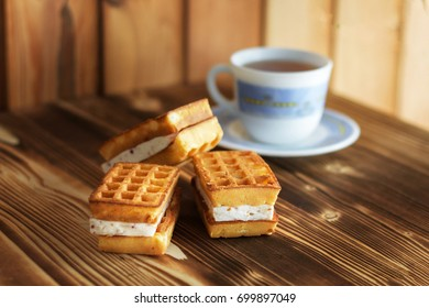 Viennese waffles and a cup of tea for breakfast on a wooden table