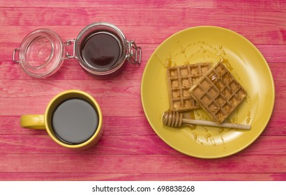Viennese waffles with mug coffee and jar honey top view