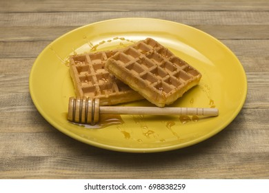 Viennese waffles on yellow plate with  honey drop