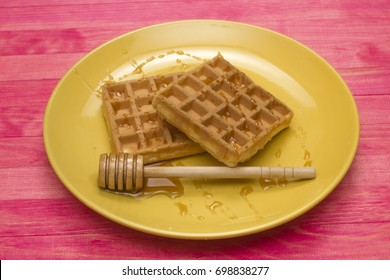 Viennese waffles on yellow plate with  honey spoon