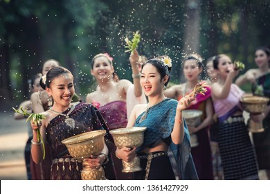 Vientiane Laos APRIL 4 2019 : Beautiful Asian woman in Laos traditionally splashing water during Water Songkran festival at Vientiane Laos.