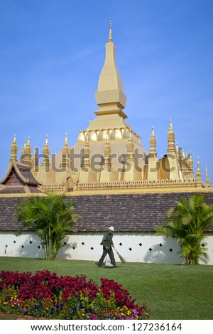 VIENTIANE, LAOS - JANUARY 12: A gardener sweeps the grounds of Pha That Luang Temple in Vientiane on 12th January 2005. Pha That Luang temple is an important symbol of Buddhism and Lao sovereignty.