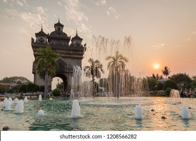 Vientiane, Laos - March 13, 2018: Fountain, palm trees, tourists and local people at the Patuxai (Patuxay), Victory Gate or Gate of Triumph, war monument in Vientiane, Laos, at sunset.