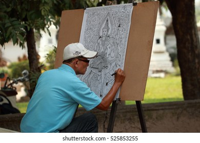 Vientiane, Laos - March 24 2016 : Man drawing picture under big tree in temple.