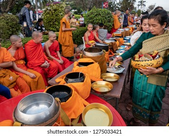 vientiane, laos - november 22, 2018: monks collecting donations before the pha that luang at the full moon festival. landmark of the country and national sanctuary.