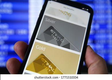 Viersen, Germany - July 6. 2020: Closeup of mobile phone with Etihad  flight booking app and loyality program. Blurred departure board background. (Focus on gold)