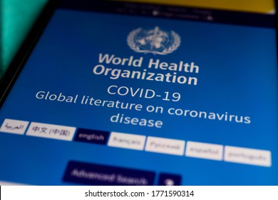 Viersen, Germany - July 7. 2020: Closeup of mobile phone screen with app of world health organization about corona virus literature (focus on covid-19)
