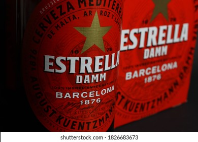 Viersen, Germany - July 9. 2020: Closeup of isolated red six pack and Estrella Damm spanish beer bottle (focus on center of bottle label)