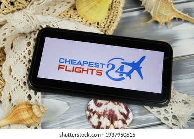 Viersen, Germany - March 1. 2021: Closeup of smartphone with logo lettering of cheapest flights 24 travel agency with sun hat and shells on wood table (focus on center of upper lettering)