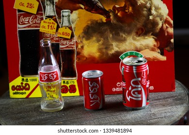 VIERSEN, GERMANY - MARCH 11. 2019: Coca Cola bottle and cans from different countries in front of an advertising cardboard from Sri Lanka with singhalese script showing Santa Claus drinking a coke