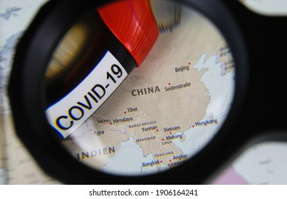 Viersen, Germany - March 28.2020: View through magnifying glass on map with focus on China and blood sample vial covid-19